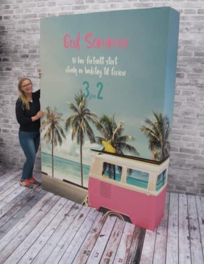 Big Box med sommermotiv og lokkende tilbud av badetøy til ferien. Kvinne står ved siden av big box-displayet for å vise hvor stort det er.