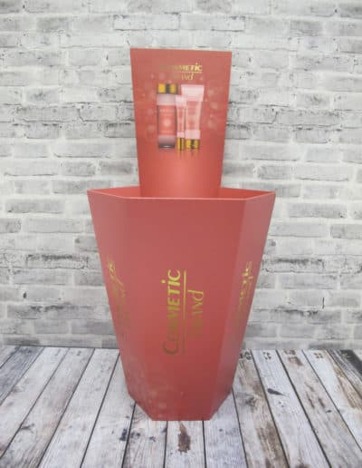 Sekskantet sjokkselger med bakplakat. Produsert i bølgepapp. Rødt motiv rettet inn mot kosmetikk-varer.
