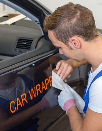 Mann folierer bil