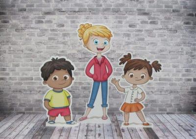 3 forskj helfigurer i bølgepapp, en gutt, en dame og en jente. Står av seg selv på tregulv.