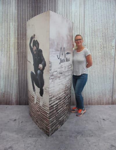 Trekantsøyle i bølgepapp med røft musikk-design. Kvinne står ved siden av for å vise hvor stor trekantsøylen er.