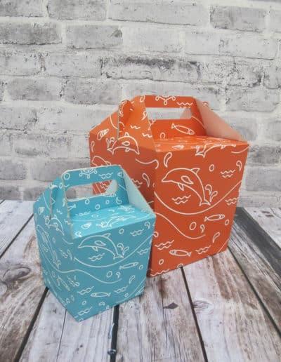2 stk koniske gaveesker med bærehank i 2 forskjellige størrelser. Den ene er turkis, den andre er oransje.