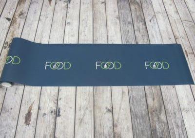 Palleskjørt i papir printet med hvit og grønn logo på blå bakgrunn. Ligger flatt på gulv, rullet ut fra rull.