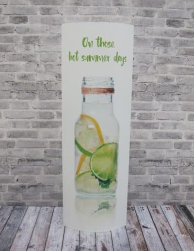 Popup med motiv av flaske med lime- og sitronvann. Står av seg selv på tregulv.