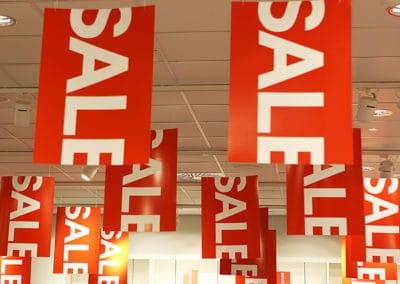 Mange takheng med salgsmotiv i rødt hengende fra tak i butikk.