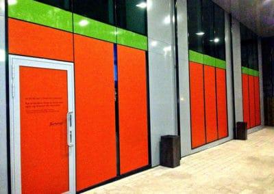 Vindudekor i innfarget oransje og grønn folie montert opp på 9 vinduer. Tekst skåret ut i sort folie og klebet oppå den innfargede folien.