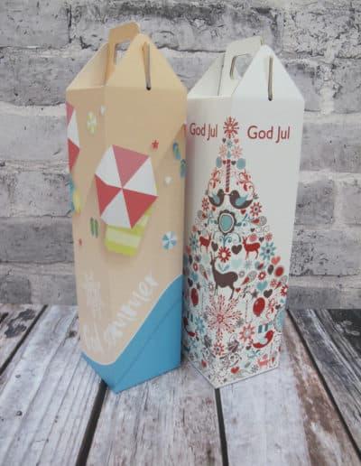 2 forskjellige gaveesker til vin. Den ene med sommermotiv og den andre med julemotiv.